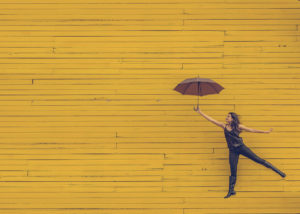 Woman jumping while holding an umbrella, on a bright yellow background.