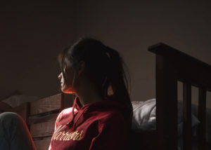 young woman sitting on floor of bedroom in the dark